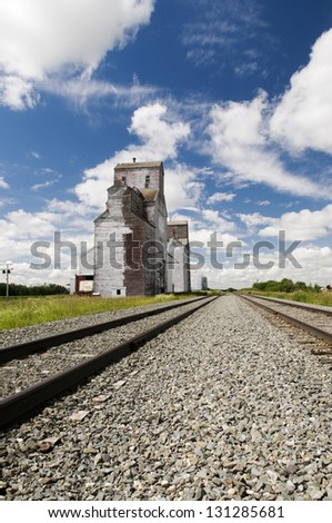 Old grain elevator located in rural Saskatchewan with railway line perspective - stock photo
