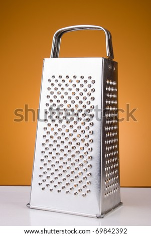 Old grater on orange background