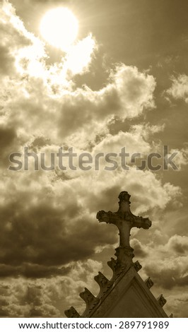 Old gravestone cross at French cemetery and sun rays glow through the clouds. Aged photo. Sepia. - stock photo