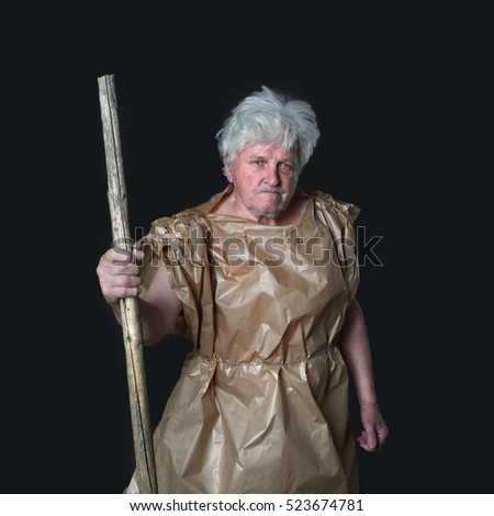 Old gray headed man dressed in tunic of wrapping paper with staff in hand on dark background in square - wanderer, pilgrim, tramp concept