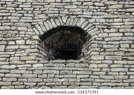 Old gray stone wall with embrasure in Krom (Kremlin) of Pskov, Russia