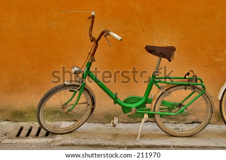 Old green bicycle against orange wall - stock photo
