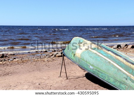 Old green boat upside down (topsy turvy) on the deserted beach against the sea and blue skies. - stock photo