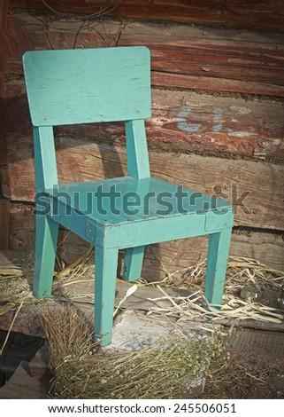 old green chair against a wooden wall - stock photo