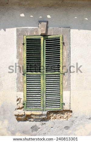 Old green closed shutters and cracked wall. Mediterranean europe architecture  - stock photo