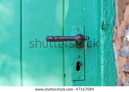 Old green door with worn iron handle in a rock wall