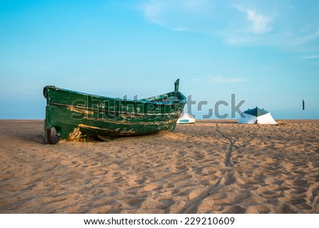 Old green fishing boat on the beach and blue sky up the horison - stock photo