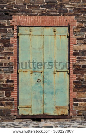 Old green weathered iron door on stone and brick