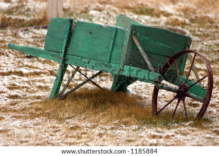 old green wheel barrow on snow frosted grass - stock photo