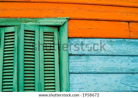 Old green window on coloured wood wall - stock photo