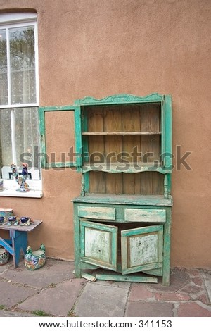 Old green wooded cabinet against a wall in a courtyard in Santa Fe, NM. - stock photo