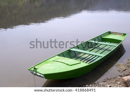 Old Green Wooden Boat Floating On The Calm Lake, Water Reflection - stock photo