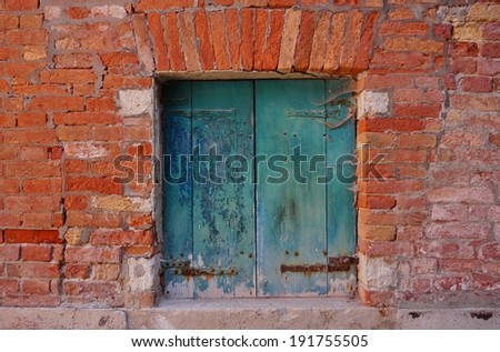 Old green wooden window in brick wall - stock photo
