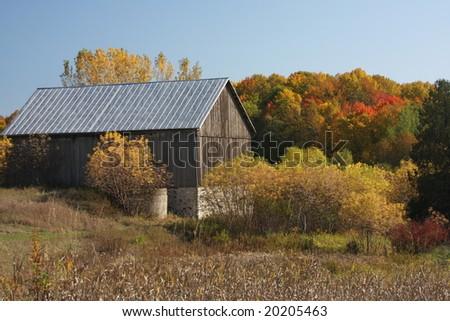 old grey barn in Wisconsin in autumn - stock photo