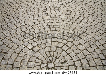 Old grey cobble stone pavement in a circle pattern in an old medieval european town.