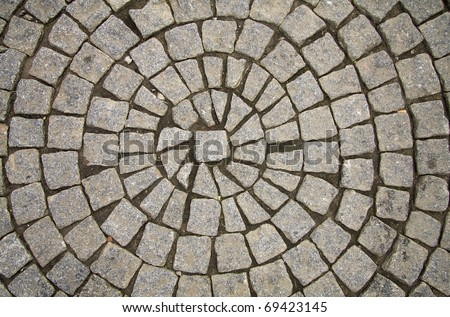 Old grey pavement of cobble stones in a circle pattern in an old medieval european town. - stock photo