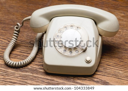 Old grey phone with rotary dial on a wooden table - stock photo