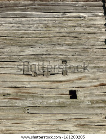 Old grey planks set horizontally with small square inlays. - stock photo