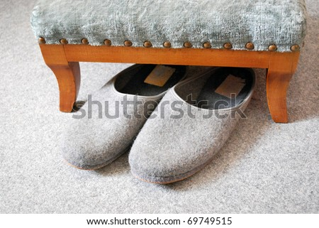 old grey slippers on carpet with stool - stock photo
