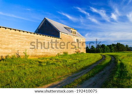 Old grey weathered barn and dirt road at sunset in Stowe, Vermont, USA - stock photo