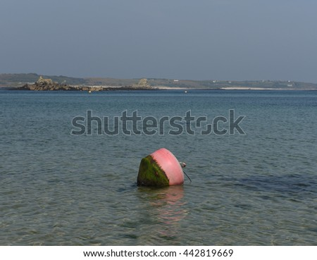 Old Grimsby Beach at Low Tide with a Pink and Black Mooring Buoy and The Island of St Martin's in the Background on the Island of Tresco in the Isles of Scilly, England, UK - stock photo