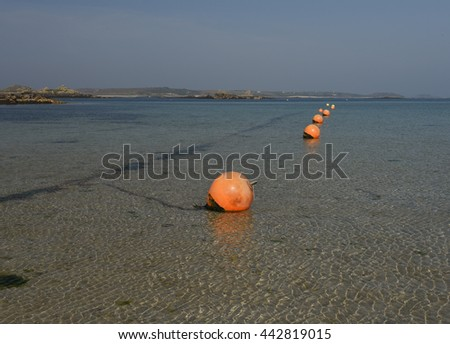 Old Grimsby Beach at Low Tide with Orange Mooring Buoys and The Island of St Martin's in the Background on the Island of Tresco in the Isles of Scilly, England, UK - stock photo