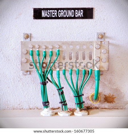 Old ground electric cables with master terminal bar. - stock photo