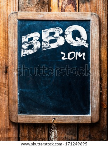 Old grunge BBQ advertising sign on an old school slate board with a distressed wooden frame and copyspace for your text mounted on wooden boards - stock photo