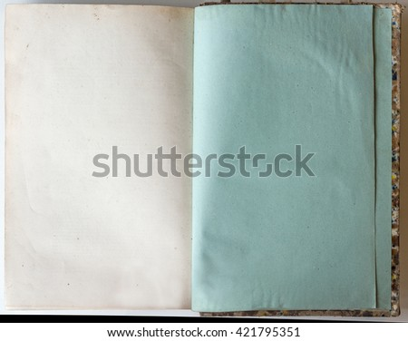 Old grunge book opened to the last page showing green aged textured paper inside. - stock photo