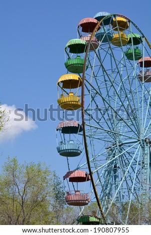 Old grunge ferris wheel against blue spring sky - stock photo
