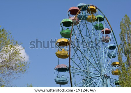 Old grunge ferris wheel against blue spring sky closeup - stock photo