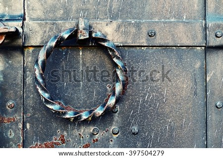 Old grunge metal door with rivets and twisted steel door handle in the form of ring. Vintage tones processing.  - stock photo