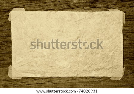 Old grunge paper on the dark wood background - stock photo