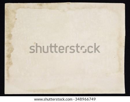Old grunge paper sheet, isolated on black background. - stock photo