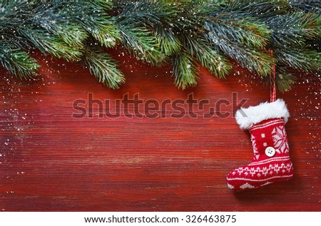 Old grunge red wooden board with Christmas border and knitted sock. Christmas card - stock photo