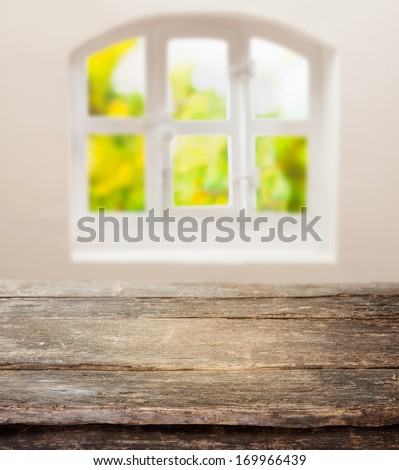Old grunge table with a weathered rustic wooden top in front of a sunny cottage pane window in a country kitchen with space for your ingredients or product - stock photo