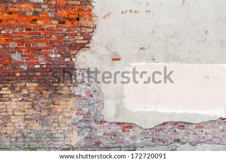 Old grunge wall background texture with bricks and stucco - stock photo