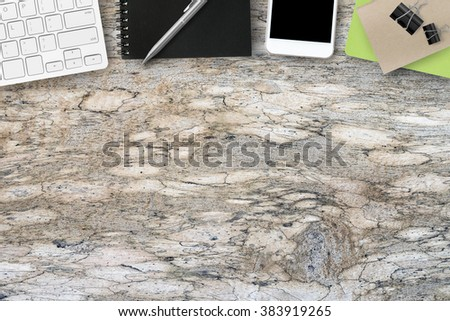 Old grunge wood table with computer keyboard, notebooks, pen and smartphone. Top view with copy space. - stock photo
