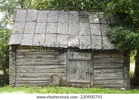 Old grunge wooden house in village background - stock photo