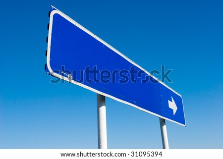 Old grungy blank signpost with direction arrow against blue sky - stock photo