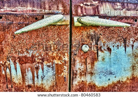 Old grungy car doors with rust and cracking, fading blue paint - stock photo