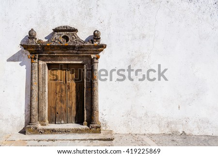 Old grungy church portal in a street of the Marvao village, Portalegre District, Alto Alentejo, Portugal. Marvao was a candidate to World Heritage Site by UNESCO. - stock photo