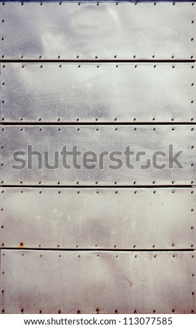 Old grungy, dirty and scratched metal plates with screws - stock photo