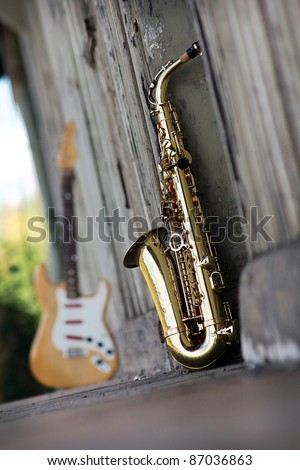 old grungy saxophone with old retro background - stock photo