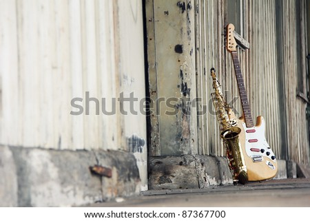 old grungy saxophone with old retro guitar - stock photo