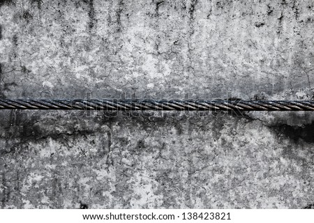 Old grungy steel cable, above old concrete wall. - stock photo