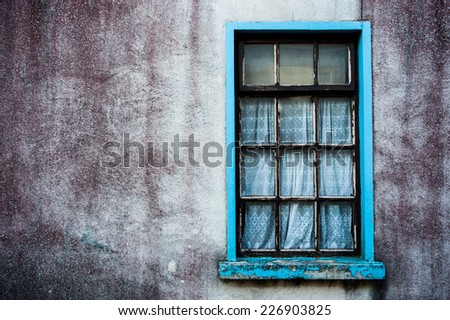 old grungy wall and window of abandoned house  - stock photo