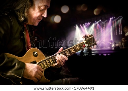 Old guitar player at concert - stock photo