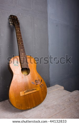 old guitar standing near the wall - stock photo