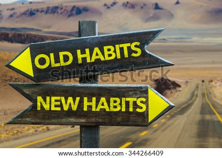 Old Habits - New Habits signpost in a desert road background - stock photo